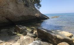 Levá strana pláže je skalnatá a najdete tu i jeskyně
